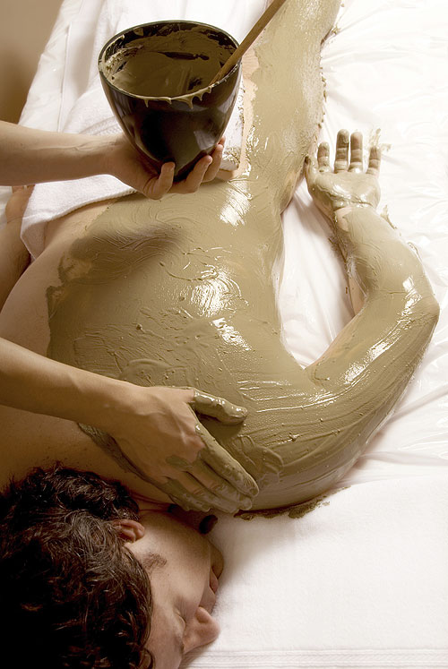 Man enjoying a spa mud wrap treatment